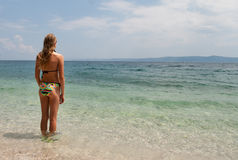 Young female in bikini facing the sea, wide view left Royalty Free Stock Photos