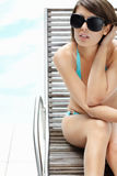 Young female in bikini sitting relaxed on recliner Royalty Free Stock Images
