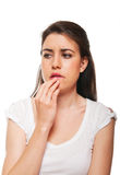 Young female biting her nails. Royalty Free Stock Photos