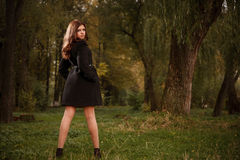 Young female in black coat. Rear view of young female in black coat posing in forest looking at camera Stock Photo