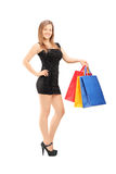 Young female in black dress holding shopping bags Stock Images