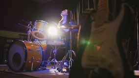Young female with black hair percussion drummer performing with drums - rock music background. Wide angle royalty free stock photo