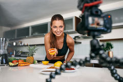 Young female blogger recording content for videoblog in Kitchen. Young woman recording food based video content on camera. Woman showing a cut orange facing the Stock Photos