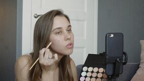 Young female blogger recording vlog video with makeup cosmetic at home online influencer on social media concept.