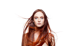 Young female with blowing hair on white. Horizontal studio beauty portrait of young attractive green-eyed caucasian female with long natural blowing shiny red Royalty Free Stock Photography