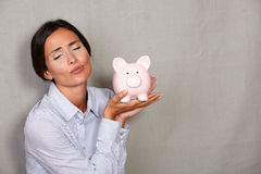 Young female blowing a kiss to piggy bank Stock Image