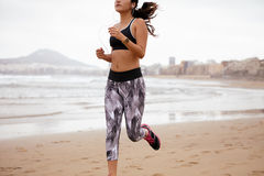 Young female body running along beach Royalty Free Stock Images