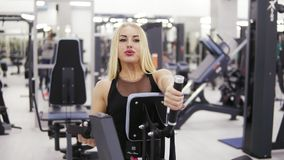 Young female bodybuilder in black sportswear doing exersices at the gym. Building up strong core and arms muscles. Frontside footage stock footage