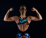 Young female bodybuilder with perfect strong muscular body wearing sportswear tracksuit posing on black background. Rear view. Royalty Free Stock Photography