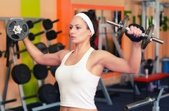 Young female bodyduilder lifting weights in the gym. Stock Image