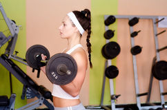 Young female bodyduilder lifting weights in modern gym Stock Images