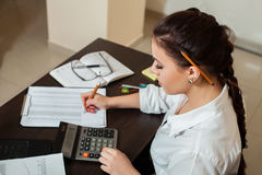 Young female bookkeeper considers on calculator. Young female bookkeeper considers on the calculator, top view on workplace with chancellery royalty free stock image