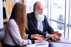 Young female boss argue old employee discuss problems in busines Royalty Free Stock Photos