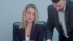 Young female boss sitting at workplace and reading paper with caucasian colleague in office stock video footage