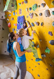 Young female bouldering instructor helping boy climb Stock Photo