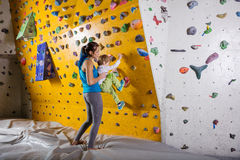 Young female bouldering instructor helping boy climb Stock Image
