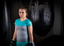 Young female boxer in boxing gloves standing near boxing punchin Stock Image