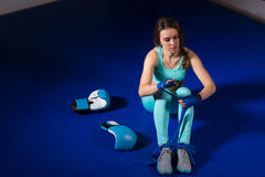 Young female boxer preparing bandages for fight near lying boxin Stock Photo