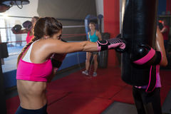 Young female boxer punching black bag stock photography
