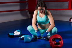 Young female boxer sitting near lying boxing gloves and helmet. In regular boxing ring in a gym Royalty Free Stock Photo