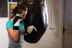 Young female boxer standing near boxing punching bag and talking Royalty Free Stock Photo