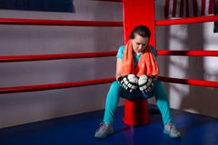 Young female boxer with a towel around her neck sitting in regul Stock Images