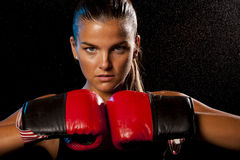 Young Female boxer in water drops. Female boxer against black background and water drops Royalty Free Stock Photo