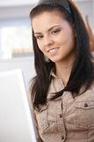 Young female browsing internet on laptop smiling Royalty Free Stock Photo