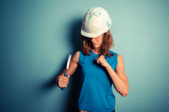 Young female builder holding a chisel aggresively Royalty Free Stock Photos
