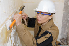 Young female builder using chisel in construction site Royalty Free Stock Image