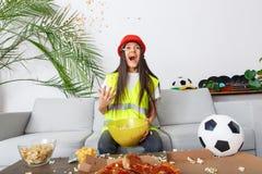 Young woman builder sport fan watching match throwing popcorn stock photo