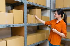 Young female business woman holding noteboard. Sweet young female business women holding noteboard checking stock goods in warehouse and looking for online Royalty Free Stock Photo
