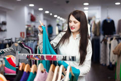 Young female buyer choosing sweater Stock Images
