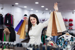 Young female buyer shopping bags. Young female buyer with bags at clothing store Royalty Free Stock Photos