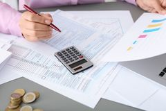 Young female calculating taxes at table, closeup royalty free stock photos