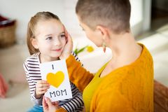 Young female cancer patient thanking her adorable young daughter for homemade I LOVE MOM greeting card. Happy Mother`s Day . Young female cancer patient stock photography