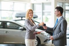Young female car sales consultant working in showroom stock photo
