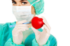 Young female cardiologist surgeron holding heart and scalpel.  Royalty Free Stock Photography