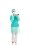 Young female cardiologist surgeron holding heart and scalpel Stock Photos