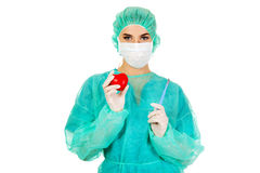 Young female cardiologist surgeron holding heart and scalpel.  stock photos