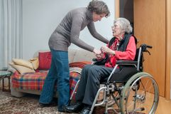 Young woman holding hand of senior woman with wheelchair royalty free stock photo