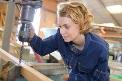 Young female carpenter using drill press in woodshop Stock Photography