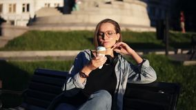 Young female in casual clothes enjoying her leisure, sitting on a street bench and licking big vanilla ice-cream. Delisious dessert. Sunny day stock footage