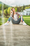 Young female in casual outfit sitting outside and listening musi Royalty Free Stock Photography