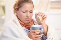 Young female caught cold drinking tea feeling bad. Young female caught cold, feeling bad, wrapped up in blanket, squeezing lemon to her tea Stock Photo