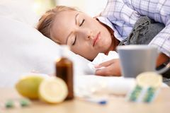 Young female caught cold laying in bed sleeping Stock Image