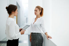 Young female ceo holding touch pad while talking with her partner in modern office interior during work break, Stock Photo