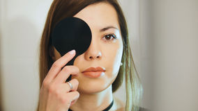 Young female checks vision in ophthalmology clinic Stock Images