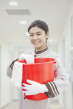 Young female cheerful caretaker holding a bucket, portrait Stock Photos