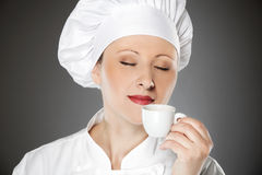 Young female chef drinking coffee Royalty Free Stock Photos